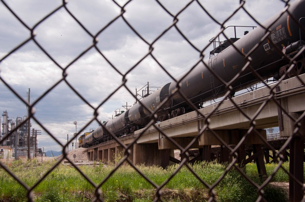 Petroleum Tankers and Refinery through Chain-Link Fence